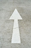 Arrow Sign On Street. White straight arrow sign on the street stock images