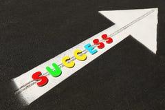 Arrow sign on the street asphalt and text success Stock Image