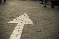 Arrow sign on the street go straight. With many walking people dark vintage tone Stock Photo