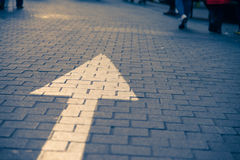Arrow sign on the street go straight. With many walking people vintage tone Royalty Free Stock Photography