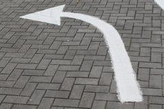 Arrow sign on street, turn left on asphalt. White Arrow sign on street, go forward on asphalt, direction to way royalty free stock photography