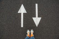 Arrow signs underfoot pattern on asphalt. Stock Photos