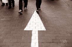 Arrow straight on pavement walking street with walking people vi. Arrow straight on pavement walking street with walking people wear jeans fashion vintage mocha Stock Images