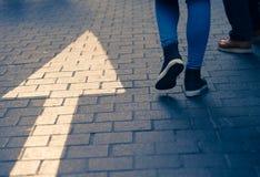 Arrow straight on street with walking people Stock Photo