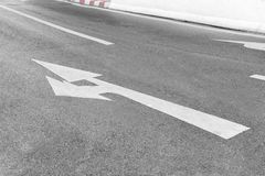 Arrow Symbol on Asphalt Road. Arrow Symbol on Asphalt Road Mandatory for direct and left Out of curves Stock Photo