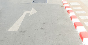 Arrow symbol on a black asphalt road surface Stock Image