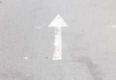 Arrow symbol on a black asphalt road surface Stock Photo