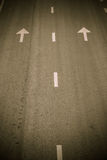 Arrow symbol and white stripes on asphalt road Royalty Free Stock Photography