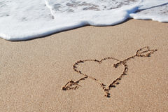 Arrow to heart in the sand. Stock Photography