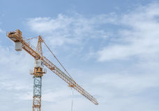 Arrow of the tower crane on the sky background. Yellow-blue tower crane close-up on a background of sky oblasnogo Stock Images