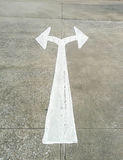 Arrow in two directions on asphalt Royalty Free Stock Photo
