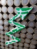 Arrow up formed with plasticine in green and white and stacked coins of mexican pesos. Trading and exchange, bank and commerce, price of buy and sell, cash value stock photo