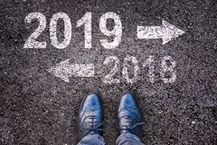 2019 and an arrow written on asphalt road background with legs. 2019 and an arrow written on an asphalt road background with legs stock photos