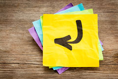 Arrow on a yellow sticky note Stock Photos