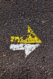 Arrow in yellow and white on a paveway Royalty Free Stock Photos