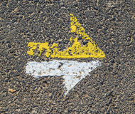 Arrow in yellow and white on a paveway for orientation Stock Images