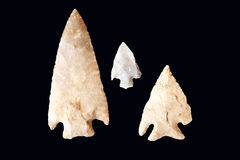 Arrowheads isolated on black. Three arrowheads of various sizes isolated on a black background Stock Photography