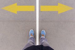 Arrows on asphalt ground, feet and shoes on floor Stock Images