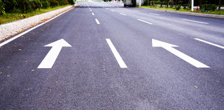 Arrows on the asphalt to indicate the direction of driving Royalty Free Stock Photo