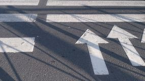 Arrows on the asphalt. White marking on the crosswalk Horizontal composition with horizontal lines and arrow Royalty Free Stock Photography