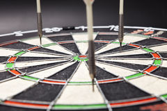 Arrows darts hit the target and are shown on a black Stock Photos