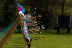 Arrows embedded in row of archery targets. Arrows sticking out from multiple targets after shooting in a competition, with flags on a windy day Stock Photography