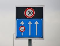 Arrows indicating the open driving lanes on motorway A12 with small lane 3 and dynamic speed limit sign of 100 kilometers. Arrows indicating the open driving stock photo