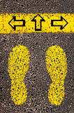 Arrows left, right, forward. Indecision Conceptual image. With yellow paint footsteps on the road in front of horizontal line over asphalt stone background stock image