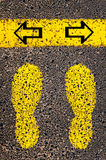 Arrows left and right. Indecision Conceptual image. With yellow paint footsteps on the road in front of horizontal line over asphalt stone background stock images