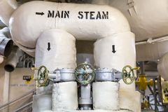 Main Steam Pipes with Multiple Valves. Arrows show direction of the main steam supply in the engine room heading to the turbine propulsion system Stock Photos