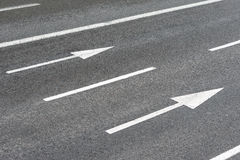 Arrows signs on an urban asphalt road Stock Photos