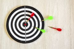 Arrows on target dart on wooden background. Top view. Royalty Free Stock Images