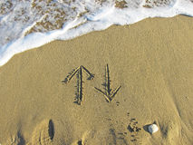 Arrows up and down drawn in the sand Stock Photo