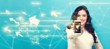 Arrows with young woman holding out a smartphone Stock Photography
