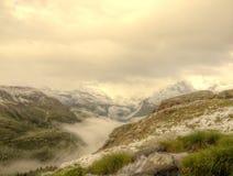 Arroyo en el prado fresco de las montañas, picos nevosos de las montañas en fondo Tiempo brumoso y lluvioso frío en montañas a fi Fotos de archivo