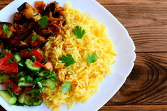 Arroz amarillo con las verduras, el ragú de la berenjena, los tomates y la ensalada del pepino en una placa blanca y una tabla de Imágenes de archivo libres de regalías