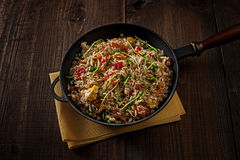 Arroz asiático delicioso en un arrabio negro con madera Fotografía de archivo