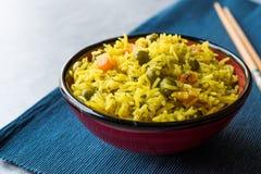 Arroz Basmati do açafrão amarelo com cúrcuma e vegetais Pilav ou pilau na bacia com hashis Foto de Stock