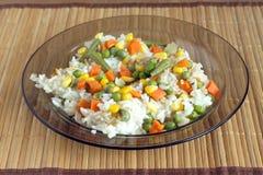 Arroz blanco con las verduras en la placa sobre la estera de mimbre Imagen de archivo
