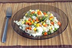 Arroz blanco con las verduras en la placa sobre la estera de mimbre Imágenes de archivo libres de regalías