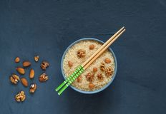 Arroz branco com porcas em uma bacia azul com os hashis isolados em um fundo escuro Alimento asiático, espaço da cópia, vista sup fotos de stock
