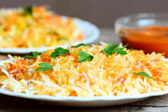 Arroz caseiro com vegetais e salsa em uma placa, salada de couve em uma placa, molho da abóbora na bacia na tabela de madeira vel Foto de Stock Royalty Free