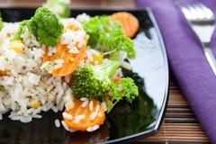 Arroz com cenouras e brócolos em uma placa preta Foto de Stock Royalty Free