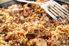 Arroz com mirtilo, carne e cenouras em um caldeirão no fogo com uma colher de prata Fotografia de Stock