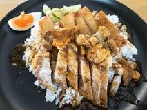 Arroz con cerdo asado y cerdo frito en el top, servicio en plato negro Foto de archivo