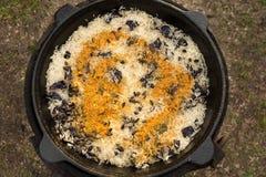 Arroz con las pasas, la paprika y el curry en una caldera en el fuego Fotografía de archivo