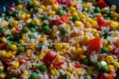 Arroz con las verduras en una cacerola Maíz dulce, paprika rojo, guisantes verdes Foto de archivo