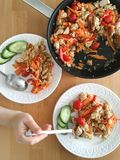 arroz con las verduras y el pollo en un sartén y en las placas para la cena Imagen de archivo