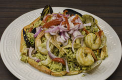 Arroz con mariscos. Peruvian Dish: Seafood green rice made of rice, cilantro with seafood medley, onions Stock Images