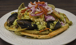 Arroz con mariscos. Peruvian Dish: Seafood green rice made of rice, cilantro with seafood medley, onions Royalty Free Stock Image